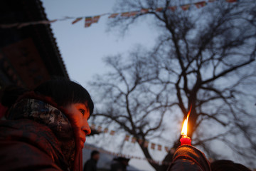 A worshipper offers a candle on the first day of Chinese New Year at Wuquanshan temple in Lanzhou