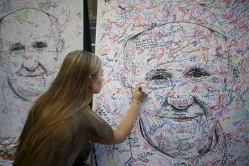 Casey Kretsch, from Minnesota, a pilgrim attending the World Meeting of Families, signs a poster drawing of Pope Francis, by artist Mark Gaines, in Philadelphia