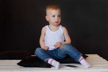 one little boy in house sitting on the floor with mobile phone  on a black background