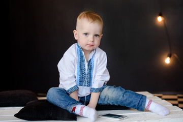 one little boy dressed in national ukrainian style clothing is sitting on black backgraund