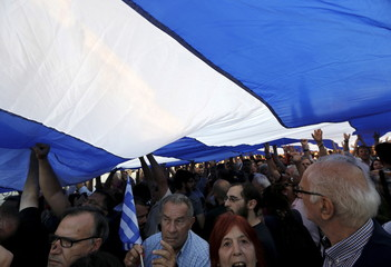 Protesters lift a huge Greek flag over the tomb of the Unknown Soldier during a rally in Athens