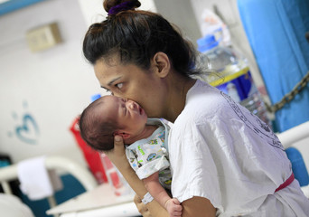 A mother kisses her newborn baby while resting inside the Fabella hospital in Manila