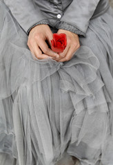 Mime artist Claudia holds an artificial red rose as she waits for an audience to perform for in central Granada
