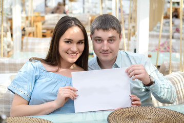 A guy and a girl looking at the camera and holding a blank piece of paper