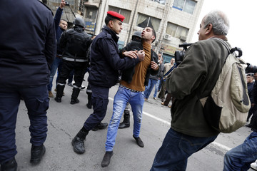 Jordanian security forces detain a demonstrator trying to reach the French embassy during a protest against satirical French weekly newspaper Charlie Hebdo, in Amman