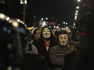 Protesters wearing Guy Fawkes masks look at the riot police during a demonstration by supporters of the Anonymous movement in Mexico City