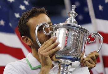 Cilic of Croatia kisses his trophy after defeating Nishikori of Japan in their men's singles final match at the 2014 U.S. Open tennis tournament in New York