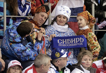Volunteer takes a picture of a family dressed in traditional Russian outfits in the spectators' stands at the women's curling round robin games during the 2014 Sochi Olympics