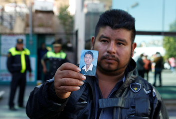 Juan Carlos Alcala holds a photograph of his son Juan Antonio, who he is being searched for after an explosion at a fireworks market, outside the Forensic Medical Service in Tlalnepantla
