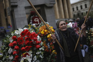 Woman holds flags as she stands at the memorial in front of the parliament building in Tbilisi