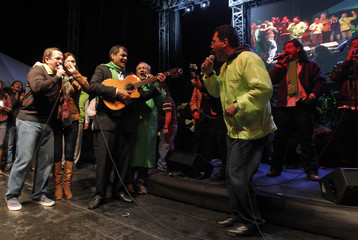 Ecuadorian President Correa is joined by supporters as he strums guitar during rally to celebrate his fifth anniversary of heading administration at Alejandro Serrano stadium in Cuenca