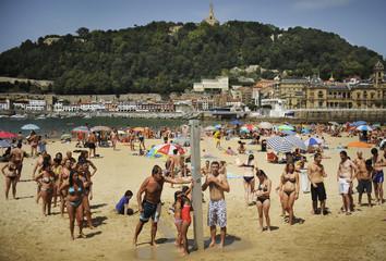 People queue to take a refreshing shower at La Concha beach in San Sebastian.