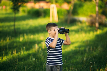 Little boy in a striped t-shirt looks through binoculars .Spring, sunny weather.