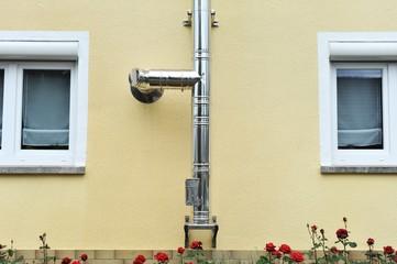 Außenkamin aus Edelstahl für Zentralheizung an einer Hauswand