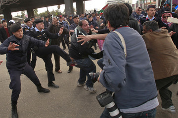 Security officers attempt to break up a clash between pro-government supporters and anti-government protesters  in Amman