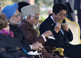 Japan's PM Abe and Indian Vice President Ansari eat during a reception at the presidential palace in New Delhi