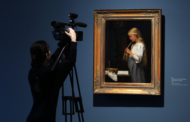 """A woman films the painting """"Maedchen, die Haare flechtend"""" by late Swiss painter Albert Anker during a media preview of the exhibition """"Beautiful World"""" in Bern"""