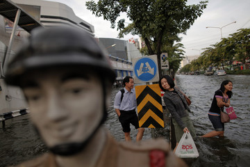 People look for transportation as the floods advance onto a major intersection with shopping malls in Bangkok
