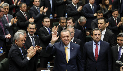 Turkey's PM Erdogan greets members of parliament from his ruling AK Party during a meeting at the Turkish parliament in Ankara