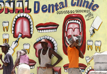 Construction workers go about their work in front of a mural advertising the various services available at a dental clinic for residents in Mogadishu