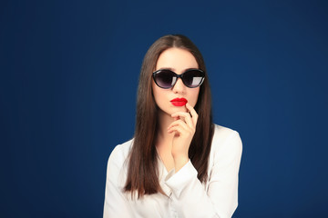 Beautiful young woman with sunglasses on color background