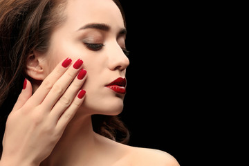 Portrait of beautiful woman with red lips on dark background