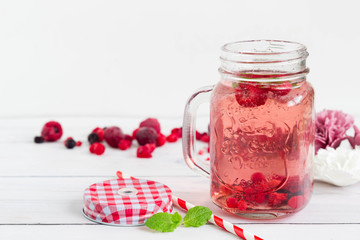 Raspberry healthy lemonade in an opened vintage mason jar with mint leaf and red paper straw placed on a white wooden board. Sugar free drink for the summer.