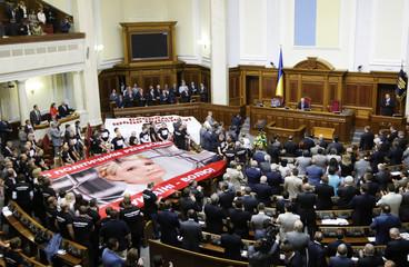 Ukraine's President Yanukovich arrives after opposition deputies unfolded a placard of former PM Tymoshenko in Kiev