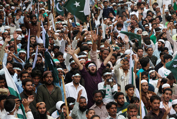 A supporter of the Difa-e-Pakistan Council, an Islamic organization, chants slogans with others during the Freedom of Kashmir Conference, in Karachi,