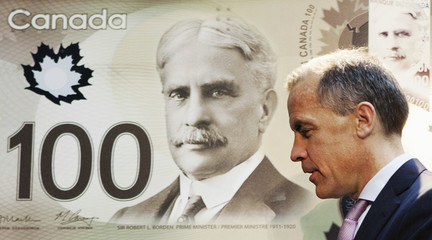 Mark Carney walks past a replication of the new Canadian 100 dollar bill made of polymer in Toronto