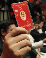A delegate of Vietnam's Communist Party raises his membership card to vote on new policies at the closing ceremony of the 11th National Congress of the Party in Hanoi
