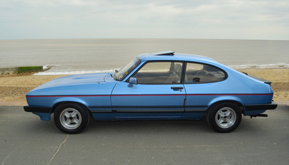 Classic Blue Capri Laser Motor Car Parked on seafront promenade.
