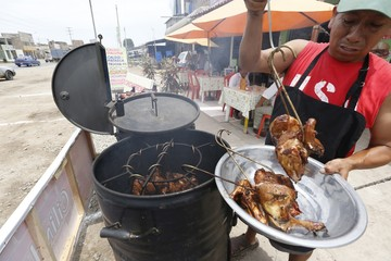 Cayo Malpartida cooks chicken and pork on a makeshift grill fashioned out of an oil barrel at Rendon Restaurant in Lurin, on the outskirts of Lima