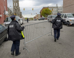 Police officers place barricades in front of the Western District police station due to anticipating a crowd of demonstrators gathering to protest the death of Freddie Gray in Baltimore, Maryland