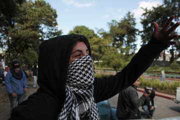 A University of San Carlos student gestures at riot policemen during a protest at the entrance of the university in Guatemala City