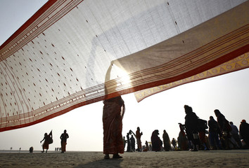 A female Hindu pilgrim dries a saree after taking a dip at the confluence of the Ganges river and the Bay of Bengal on the occasion of Makar Sankranti festival at Sagar Island