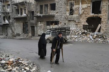 Residents walk beside damaged buildings in Aleppo