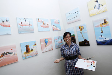 Painter MaryAnn Loo poses with her art pieces in her home in Singapore