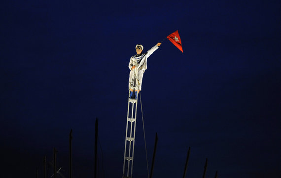 An actor holds a flag during a re-enactment of the sinking of the luxury liner RMS Titanic in Carlilse
