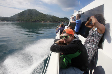 Tourists travel on a boat to the island of Koh Tao, where two British tourists were killed earlier this week
