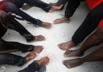 Shoeless migrants are seen onboard a rescue craft during a rescue operation, as lifeguards from the Spanish NGO Proactiva Open Arms rescue all 112 on aboard a drifting raft