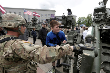 Boy inspects U.S. army weapon during tactical road march Dragoon Ride II display in Daugavpils