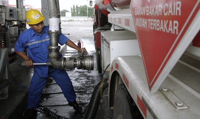 A worker refuels a tank truck, before it leaves to transport fuel to gas stations, at the Pertamina refueling depot in Jakarta