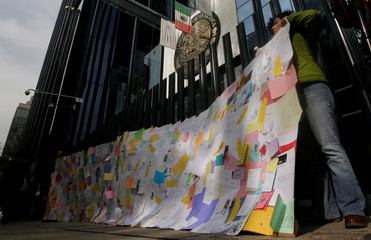 Activists hold up thousands of letters, notes and Christmas cards sent by people in support of Miriam Lopez, a victim of torture in Mexico, as they block the Attorney General's office during a protest in Mexico City