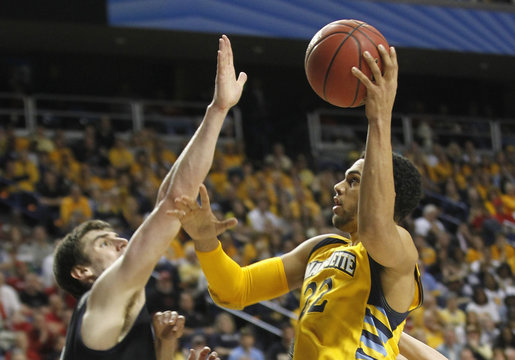 Marquette University's Lockett fights to get shot off under pressure from Butler University's Smith during NCAA basketball in Lexington