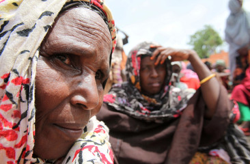 Internally displaced women wait to receive relief food from a distribution point in Somalia's capital Mogadishu