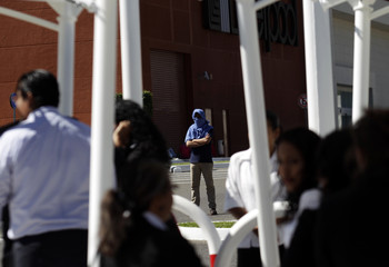 A hooded student looks at employees of shopping mall who evacuated the building earlier, during a protest in Chilpancingo