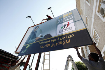 Workers put up an election campaign poster of Dr Mahmoud Jibreel in Tripoli
