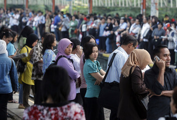 People stand as they wait for a commuter train in Depok, Indonesia's West Java province