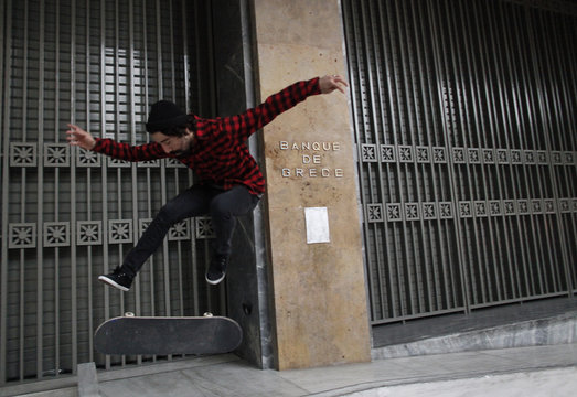 A man performs a manoeuvre with his skateboard outside the Central Bank of Greece in Athens